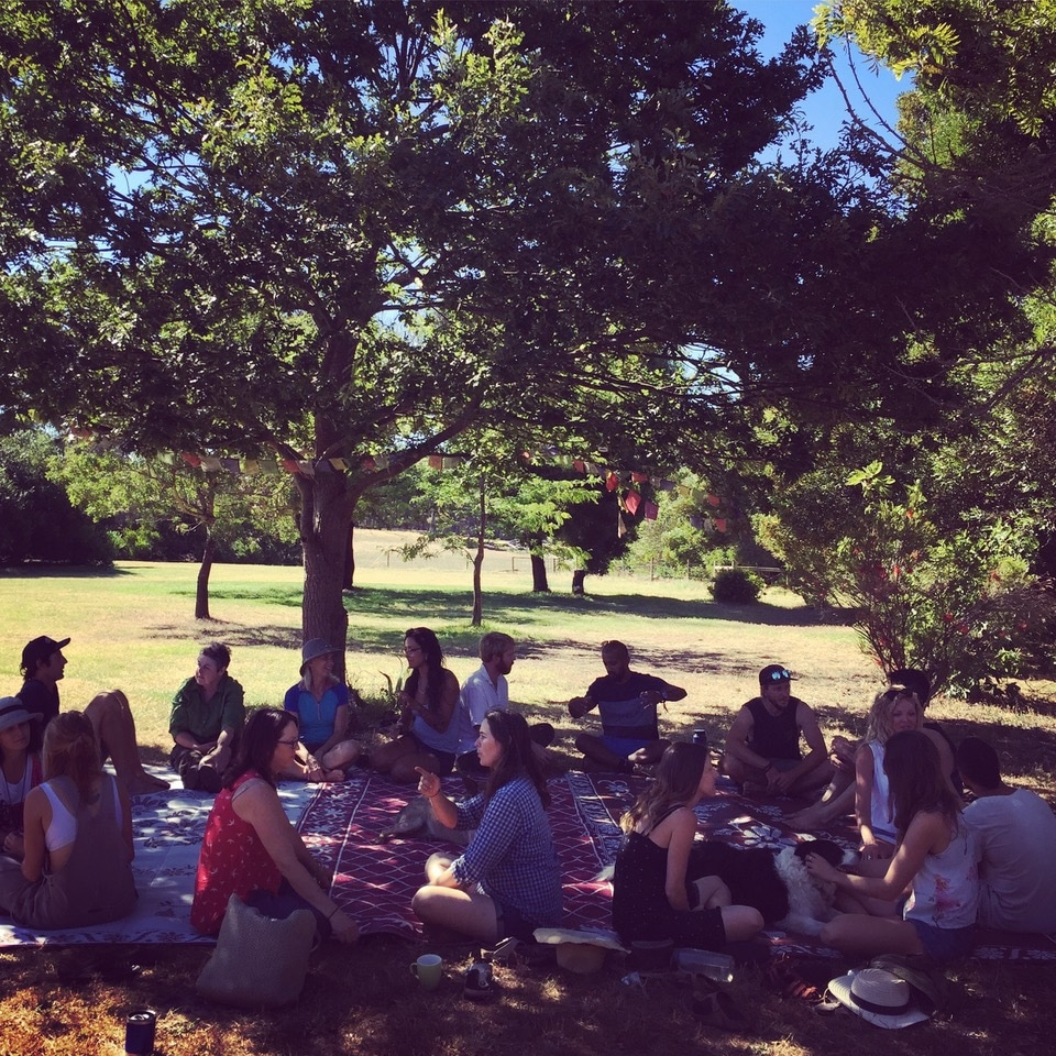 Photograph of students sitting together under an oak tree.